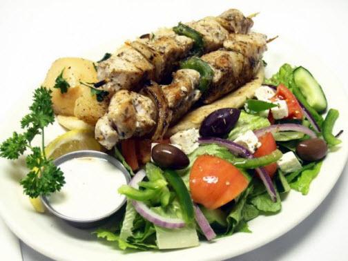 Athens classic Chicken Souvlaki dish! Warm seasoned chicken, served with fresh Greek salad